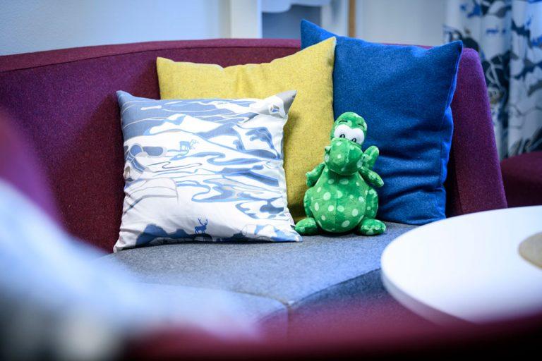 Soffa med kuddar och gosedjur i väntrum i Barnahus lokaler
